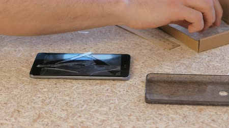 smashing : Man changes the cracked safety glass of the mobile phone the new.