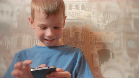 boyish : Smiling seven-year-old boy playing games on his mobile phone.