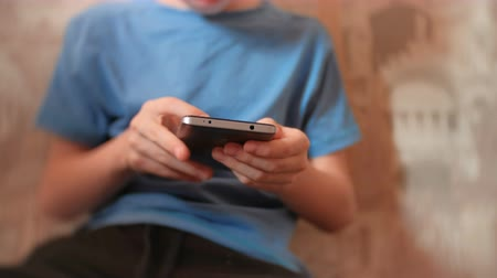boyish : Unrecognizable seven-year-old boy browsing internet on his mobile phone. Stock Footage