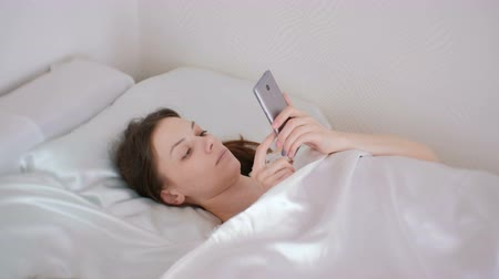 ebook : Woman reads something in her phone while lying in bed in the morning.