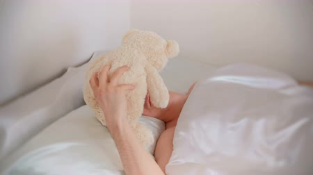 пуховое одеяло : Young father dad wakes up and finds a toy bear in bed after a hard night with a child. Стоковые видеозаписи