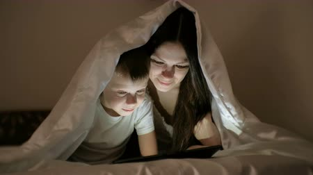 sobressalente : Young woman mom and her son watching a film together on tablet under the blanket.