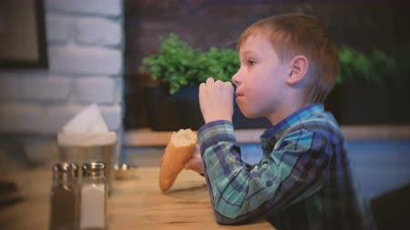 harmful : Boy eats a baguette and watches TV in the cafe. Side view.