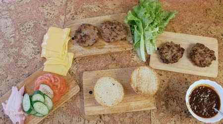 kepekli : Products for preparation of burgers: buns, tomatoes, cucumbers, cutlets, cheese, salad, sauce, bacon on the table. Top view. Stok Video