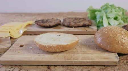 cheese making : Products for preparation of burgers: buns, cutlets, cheese, salad, on the table. Side view. Stock Footage