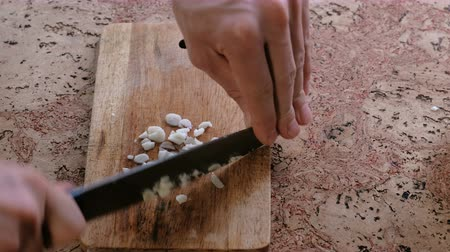 blurring : Man cuts garlic on a wooden board. Close-up mans hands.