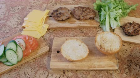 bacon burger : Products for preparation of burgers: buns, tomatoes, cucumbers, cutlets, cheese, salad, sauce, bacon on the table.