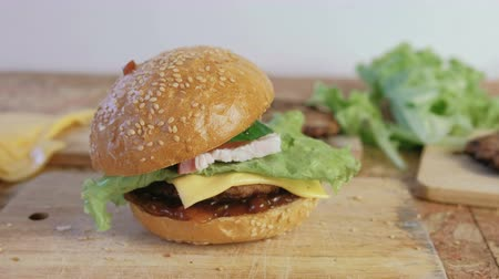 kepekli : Homemade burger with buns, cutlets, cheese, salad, on the wood board.
