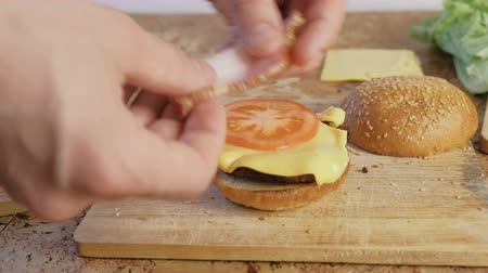 kepekli : Man makes burger with buns, tomatoes, cucumbers, cutlets, cheese, salad, sauce, bacon. Close-up hands,