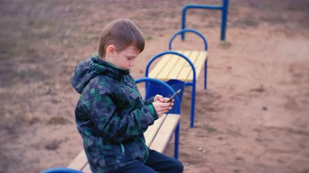 learning to walk : Boy types a message on his mobile phone sitting on the bench in park.