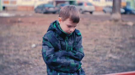 refah : Sad boy sitting on a bench. Boy is lost and waiting for parents.