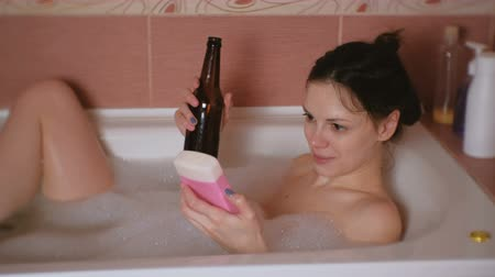 buborékok : Young beautiful brunette woman takes a bath and drinks beer. Reads inscriptions on bottle shampoo. Stock mozgókép