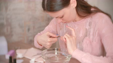 püskül : Woman cuts cuticle with nipper. Makes manicure herself. Manicure tools on the table.