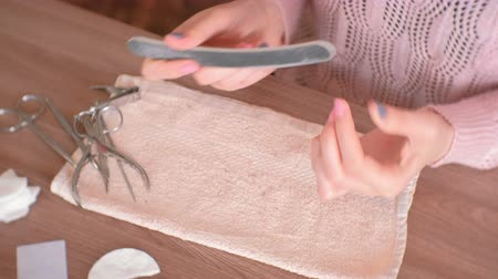 emery : Woman filings nails nail file. Close-up hands. Tools on the table. Stock Footage
