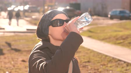 çok katlı : Young woman brunette in sun glasses drinks water from the bottle on the street. Opens the bottle, drinks water and closes the bottle. Stok Video