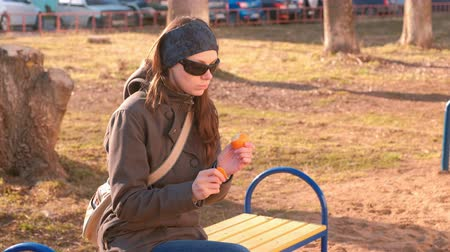 unpeeled : Young brunette woman in sunglasses peels and eats tangerine sitting on the bench in park.