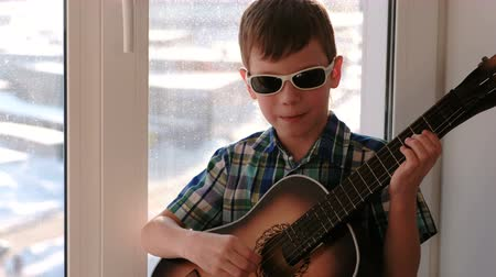 gitáros : Playing a musical instrument. Boy in sunglasses plays the guitar and singing sitting on the windowsill. Stock mozgókép