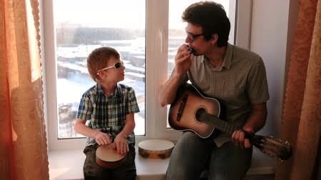 tambourine : Playing a musical instrument in sunglasses. Dad is playing the guitar and son is playing drum sitting in windowsill