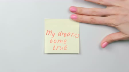 fráze : Closeup womans hands stick yellow sticker paper sheets with words my dreams come true. Dostupné videozáznamy
