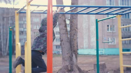 monkey : Boy crawling on the monkey bars in the yard of a city house. Games and walks on the Playground. Stock Footage