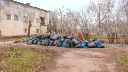 arrumado : Black trash bags piled up In the city against house.
