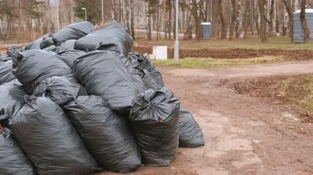 accumulation : Close-up of black trash bags piled up In the city park. Stock Footage