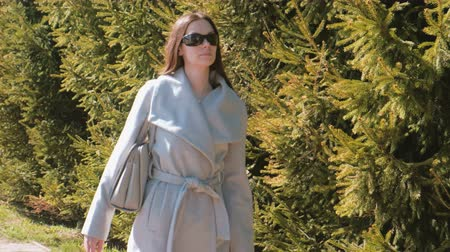 timeout : Young brunette woman in sunglasses and coat walks in city park among the trees.