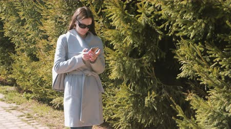 timeout : Young brunette woman in sunglasses and coat walks in city park and looks at phone.