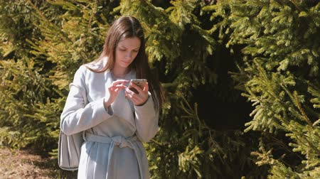 timeout : Young brunette woman in coat looks at the navigation map in your phone to find the path in the city Stock Footage