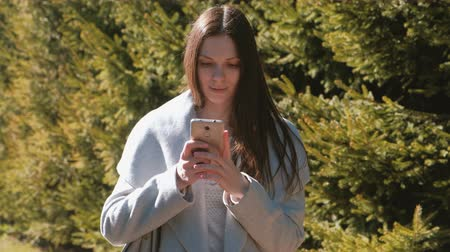 timeout : Portrait of beautiful brunette sending a message in her phone in park. Side view.