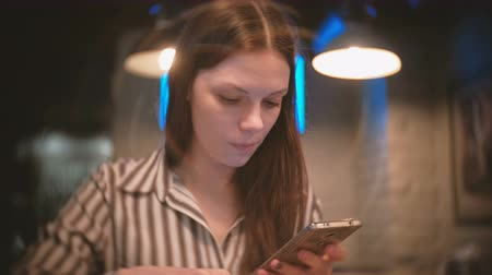 fries : Woman is browsing internet in her mobile phone and eating French fries. Stock Footage
