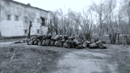 törmelék : Black trash bags piled up In the city against house. Black and white. Stock mozgókép
