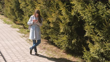 timeout : Young brunette woman in coat looks at the navigation map in your phone to find the path in the city. Stock Footage