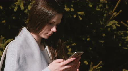timeout : Portrait of beautiful brunette reading a message in her phone in park. Side view.