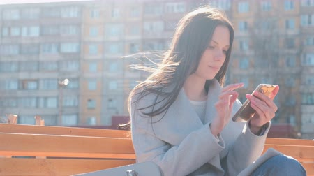 timeout : Portrait of beautiful brunette typing a message in her phone in the courtyard of a multi-storey building.