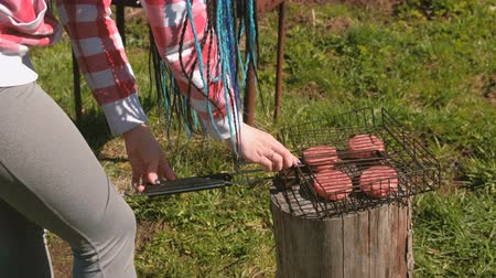 blue braid : Unrecognizable young woman closes the grill with the chops. Close-up hands. She is in plaid pink shirt and with blue braid hairs.