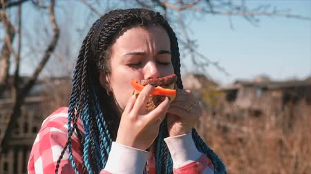 unhealthy eating : Young woman with blue braid hairs eats sandwich with bread, cutlet, pepper and cheese outdoor.