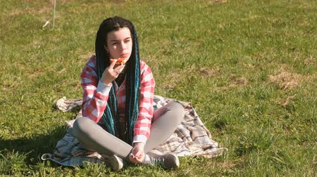 blue braid : Young woman brunette eats sandwich in picnic on park. Stock Footage