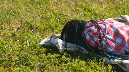 blue braid : Unrecognizable woman with blue African braids sleeping on the lawn in the Park.