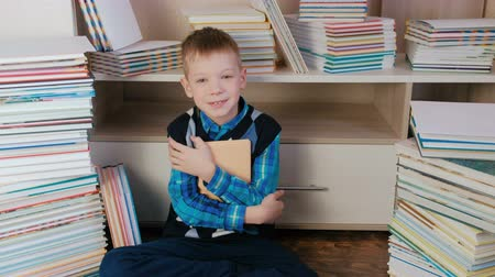 ciltli : Seven-year-old boy hugging the book and smiling at the camera sitting among books. Closeup.