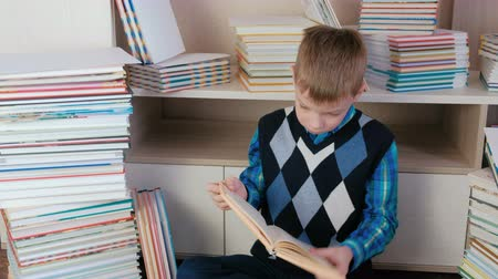 ansiklopedi : Seven-year-old boy takes the book out of the stack and read sitting among books.