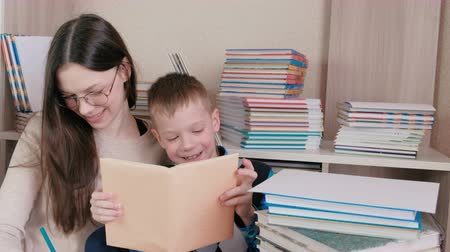 tome : Mom and son read a book together. Mom in glasses. Stock Footage