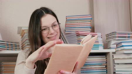 ansiklopedi : Young brunette woman in glasses smiling reading a book. Sitting among the books.