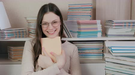 tome : Young brunette woman in glasses laughs hugging a book sitting among books. Stock Footage