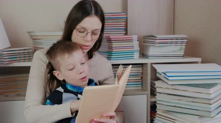 alfabetização : Mom and son read a book together. Mom in glasses. Vídeos