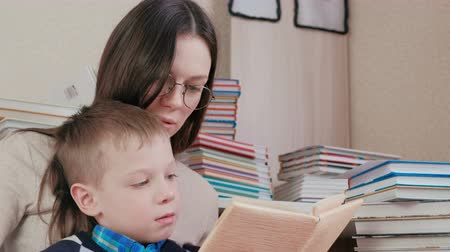 ciltli : Mom and son read a book together. Mom in glasses. Closeup faces. Stok Video
