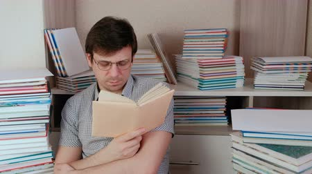 ansiklopedi : Young brunet man in glasses reads a book sitting among books.