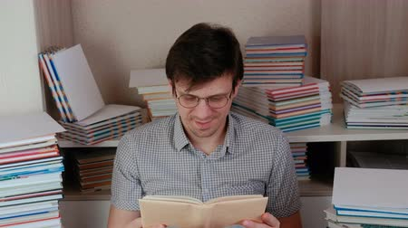 tome : Young happy brunet man puts on his glasses and reading a book. Stock Footage