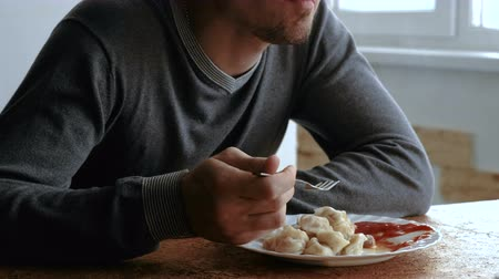 bakalář : Man eats dumplings with a fork, putting them into tomato sauce in the kitchen Dostupné videozáznamy