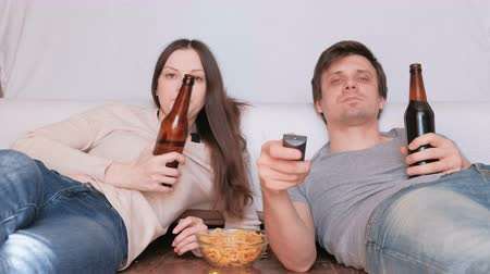 watch tv : Couple of young man and woman eating chips drinking beer and watching TV, switching channel. Talking and smiling